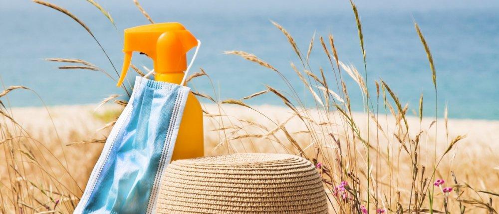 Na zdjęciu plaża, kapelusz i okulary słoneczne.