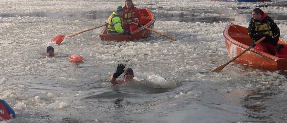 Na zdjęciu zmarznięty staw, po stawie pływa łódka w niej 2 ludzi, w stawie morsują ludzie.