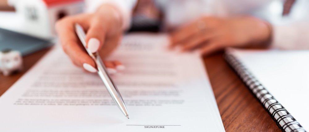 Kobieta wsakazuje długopisem miejsce podpisania umowy.