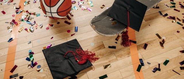 Na zdjęciu parkiet w sali gimnastycznej, piłka do kosza, deskorolka i birety uczniowskie oraz rozsypane konfetti na parkiaecie.