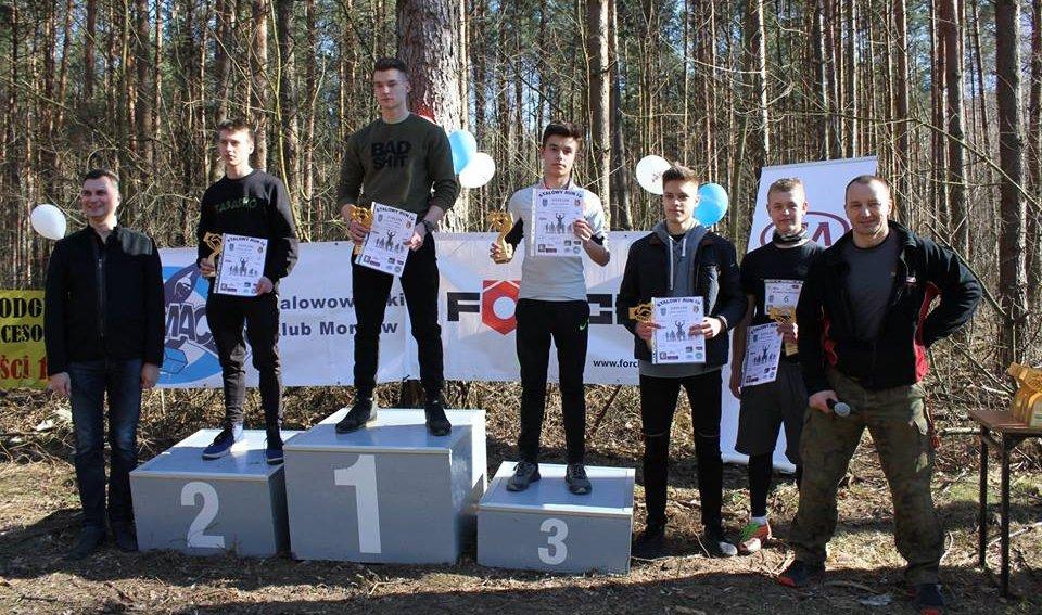 Na zdjęciu uczestnicy biegu Stalowy Run. Trzech zawodników na podium, dwóch wyróżnionych z prawej strony oraz organizatorzy biegu.