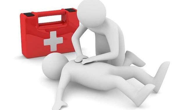 Na zdjęciu przedstawiona pierwsza pomoc, dwoje ludzi i apteczka.
