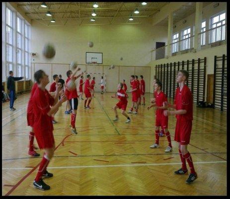 Uczniowie na sali gimnastycznej w trakcie zajęć siatkówki.