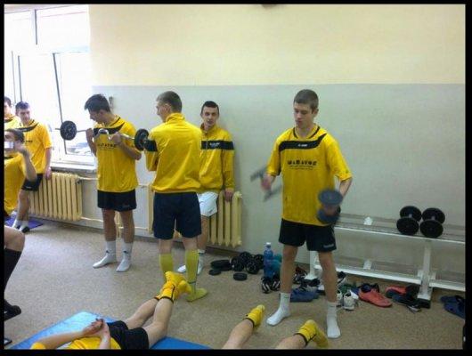Uczniowie w żółtych strojach sportowych na siłowni.