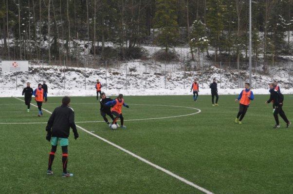 Uczniowie klasy piłkarskiej w trakcie treningu na boisku.